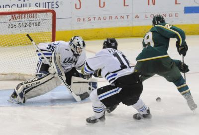 Carmine Guerriero makes a save as Brent Fletcher chases the puck against Alaska Anchorage in the 2014-15 season.